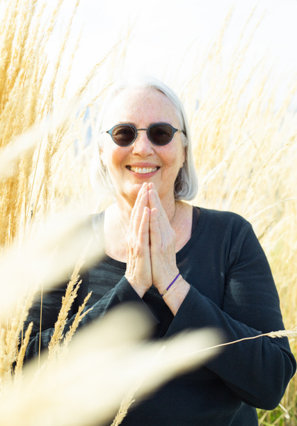 Maggie Mackenzie wears a black sweater and sunglasses in a golden field of wheat with a smiling and gracious expression