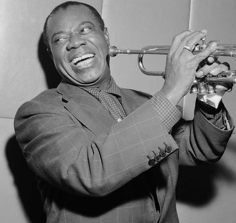 Black and white photo of Louis Armstrong smiling between blasts of his trumpet