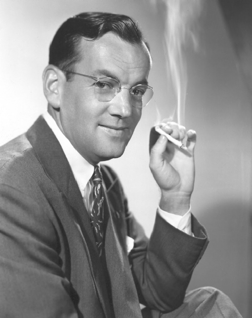 Black and white photo of Glen Miller smoking a cigarette in a suit